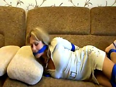 Hogtied girl struggles from couch to door