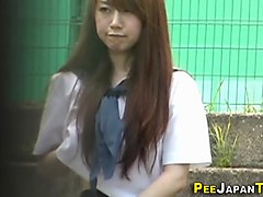 an asian teen student is taking a piss in the public and voyeur is spying on her