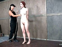 submissive redhead gets tied up in standing position by domme